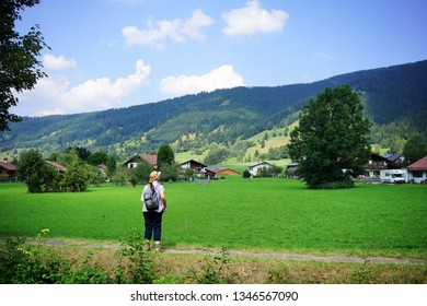 Oberammergau, Bavaria / Germany - August 20, 2018: Senior female hiker enjoying beautiful sunny summer day view of alpine meadows and rolling hills from valley path.