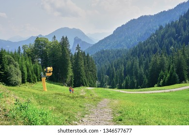 Oberammergau, Bavaria / Germany - August 20, 2018: Man and Boy hiking in beautiful green alpine meadow with forest and distant hazy mountains in background on sunny day.