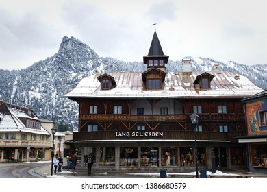 """Oberammergau, Germany, March 23, 2018 - The traditional wood carving store """"Lang Selig Erben"""" before a snow covered mountain in Bavaria"""