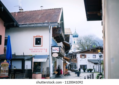 Oberammergau, Germany - March 30, 2018 : Beautiful view of old town city and building paintings with church in background. People shopping on main street in Oberammergau, Germany, Europe