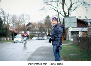 Oberammergau, Germany - March 30, 2018 : Asian man standing on main street in Oberammergau with beautiful view of old town city in background, Oberammergau, Germany