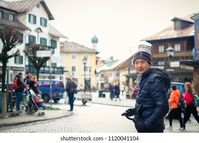 Oberammergau, Germany - March 30, 2018 : Asian man standing on main street in Oberammergau with beautiful view of old town city and building paintings in background, Oberammergau, Germany