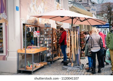 Oberammergau, Germany - March 30, 2018 : People shopping in souvenir on main street with beautiful building painting in background, Oberammergau, Germany, Europe