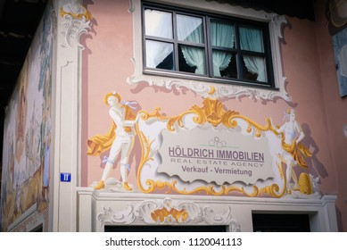 Oberammergau, Germany - March 30, 2018 : Beautiful view of old town city and building paintings. People shopping on main street in Oberammergau, Germany, Europe