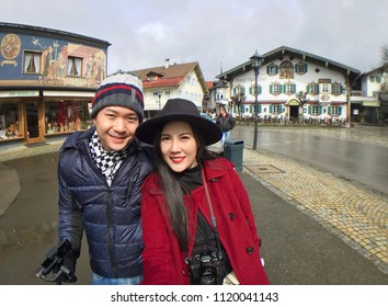 Oberammergau, Germany - March 30, 2018 : Young couple lover with beautiful view of old town city and building paintings in background, Oberammergau, Germany