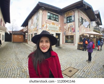 Oberammergau, Germany - March 30, 2018 : Asian woman standing on main street in Oberammergau with beautiful view of old town city and building paintings in background, Oberammergau, Germany