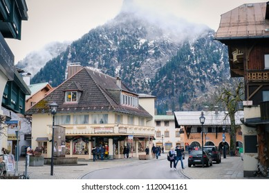 Oberammergau, Germany - March 30, 2018 : Beautiful view of old town city and building paintings. People shopping on main street with the mountain background in Oberammergau, Germany, Europe