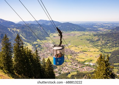 OBERAMMERGAU, GERMANY - MAY 26: People in a cable car on the Laaber mountain over the village of Oberammergau, Germany on May 26, 2017.