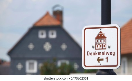 "Obercunnersdorf, Oberlausitz / Germany - June 21, 2019: Sign stating ""Denkmalweg"", (trail of architectural monuments) in Upper Lusatia, with typical house in background"
