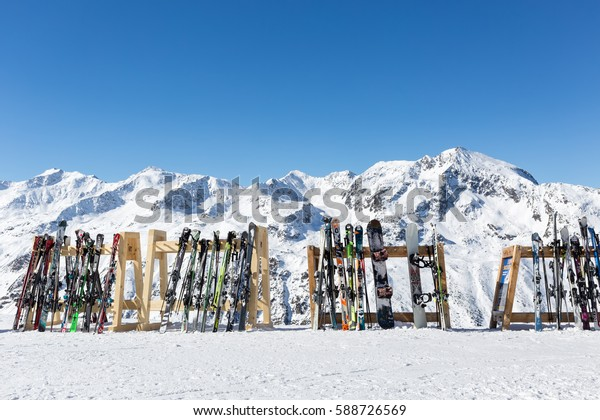 OBERGURGL, AUSTRIA - FEBRUARY 19, 2017: A line of skis and snowboards stored on racks outside a cafe on the slopes at Hochgurgl with the Otztal Alps in the background.
