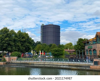 Oberhausen (Centro, ruhrgebiet), Germany - July 9. 2021: View over water canal beyond beach and bridge on gasometer tower against summer sky, green trees in park