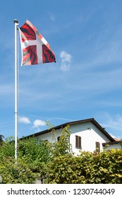 Oberhofen/Switzerland - August 25 2015: Canton Swiss flag at a house in the village of Oberhofen, Switzerland.