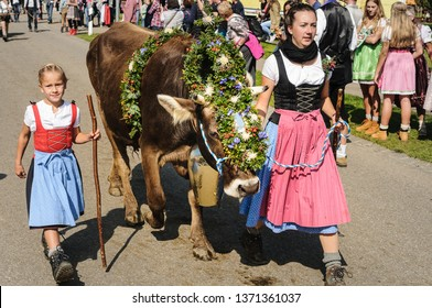 OBERMAISELSTEIN, BAVARIA / GERMANY - SEPTEMBER 23 2017: young girl and woman wearing Dirndl with adorned cattle at the traditional annual Almabtrieb / Viehscheid in Allgaeu