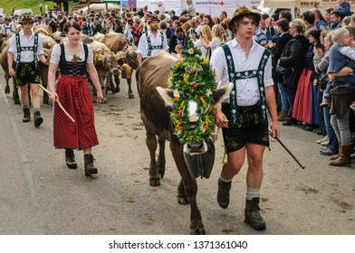 OBERMAISELSTEIN, BAVARIA / GERMANY - SEPTEMBER 23 2017: woman waring dirndl and men wearing lederhosen with adorned cattle at the traditional annual Almabtrieb / Viehscheid in Allgaeu