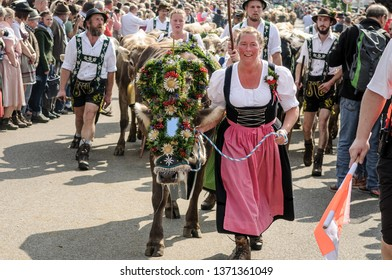 OBERMAISELSTEIN, BAVARIA / GERMANY - SEPTEMBER 23 2017: woman wearing dirndl with adorned cattle at the traditional annual Almabtrieb / Viehscheid in Allgaeu