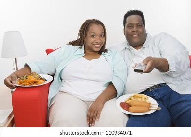 Obese African American couple eating junk food