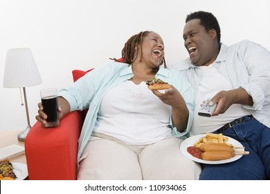 Obese African American couple sitting together with plates of junk food