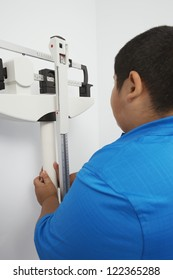 Obese boy measuring weight on scales in clinic