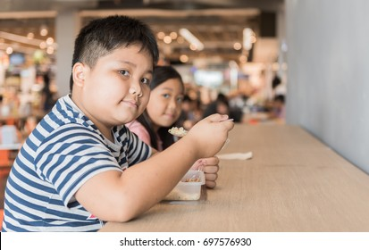 Obese brother and sister eating box lunch in food court, fastfood concept