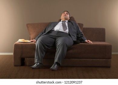 Obese businessman in formal clothes sleeping on sofa with plate of burgers and french fries