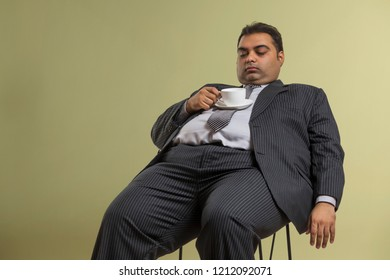 Obese businessman in formal clothes sleeping on chair with tea cup and saucer on his stomach