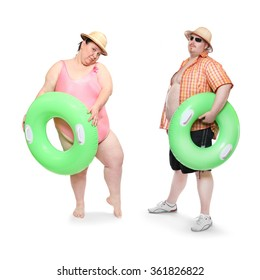 Obese couple in swimsuit with green lifebuoy. Funny people enjoying holidays on the beach. Studio shot of two persons on white background.