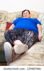 Obese elderly casual woman sleeping on sofa.