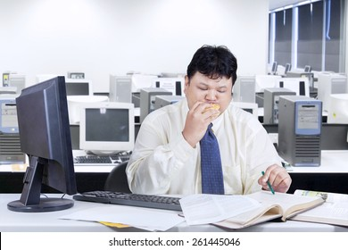 Obese entrepreneur working on table while biting a burger, shot in the office