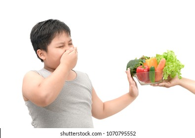 Obese fat boy with expression of disgust against vegetables isolated on white background, Refusing food concept