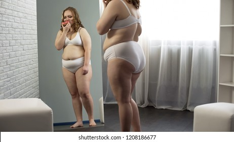 Obese girl crying and eating donut, hopeless trying to lose weight, overweight