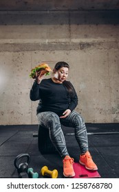 obese girl without motivation sitting on the barbell and looking at the floor scales. lazy overweight woman cannot loss her weight as she is gourmand, guttler. full length shot