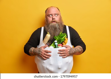 Obese greedy man stocks foodstuff, eats too much, suffers from overweight and gluttony, keeps hands on belly full of products, has tattooed arms, thick beard, concentrated with frightened look