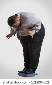 Obese man in formal clothes standing on a weighing machine bending forward shocked to see his weight