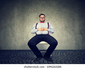 Obese man in formal outfit having sedentary way of living looking lazy on gray background.