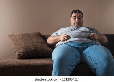 Obese man sitting on sofa holding his belly fat with both hands and looking sad