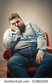 Obese man sitting in a red armchair
