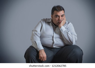 Obese man sitting in sad mood with chin resting on hand