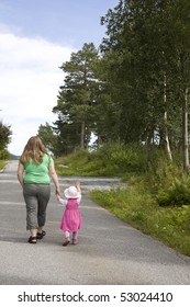 Obese mother and child walking on a forest path on a beautiful summer day.