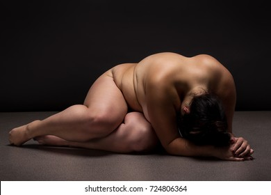 Obese nude woman doing yoga exercise. Morning Workout. Sport concept.