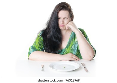 Obese woman with black hair sitting in front of a plate with a single green pea, she looks frustrated in the camera, against a white background.