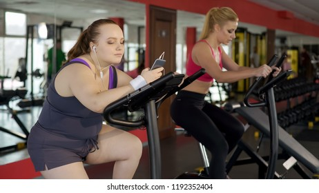 Obese woman listening music on phone while lazily riding stationary bike in gym