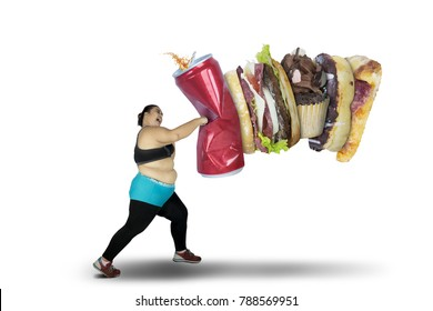 Obese woman punching unhealthy food while wearing sportswear, isolated on white background