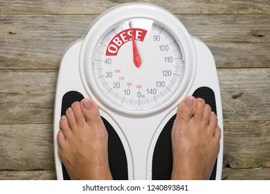 Obese woman standing on  analog bathroom scale, view from the above