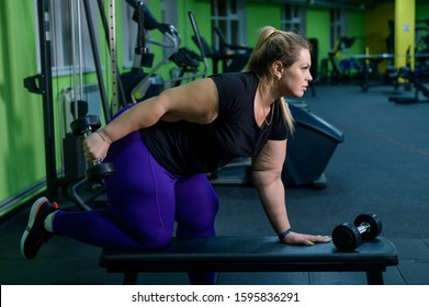 An obese woman is training with dumbbells on a bench in the gym. The fat blonde is losing weight with the help of fitness.