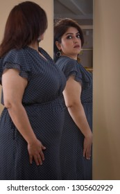 Obese Woman trying dress in looking in mirror
