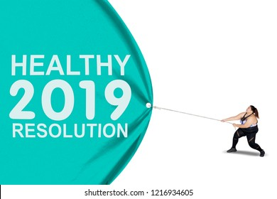 Obese woman wearing sportswear while pulling text of healthy resolution for 2019 on a banner, isolated on white background