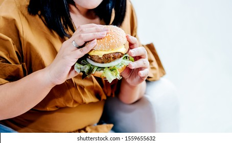 Obese women are happy With eating hamburgers, which consist of meat, fresh vegetables, breads and cheese with white background, to food and healthy concept.