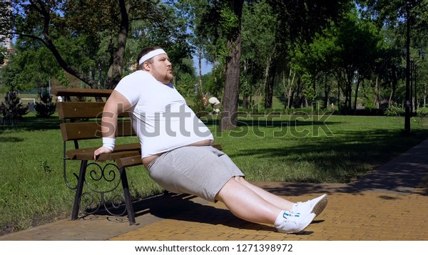 Obese young man exercising on bench, outdoor workouts, struggle to slim down