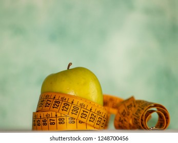 Obesity concept. A green apple and a tape measure on top of a table