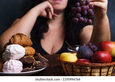 Obesity prevention, conscious eating, nutrition choices, mindfulness and healthy lifestyle. Cropped portrait of overweight woman choosing between junk sweet food and fruits